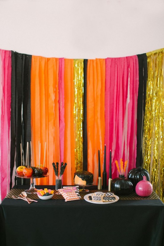 super bright Halloween decor - a bold striped backdrop with glitter touches, a black table with pink and black pumpkins and bold sweets