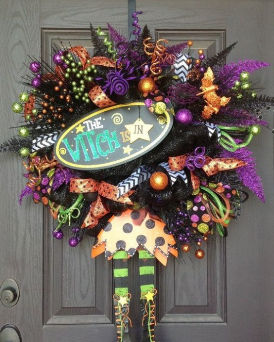a super colorful Halloween wreath in orange, purple and green, with ribbons, berries, ornaments and witches' hats and legs