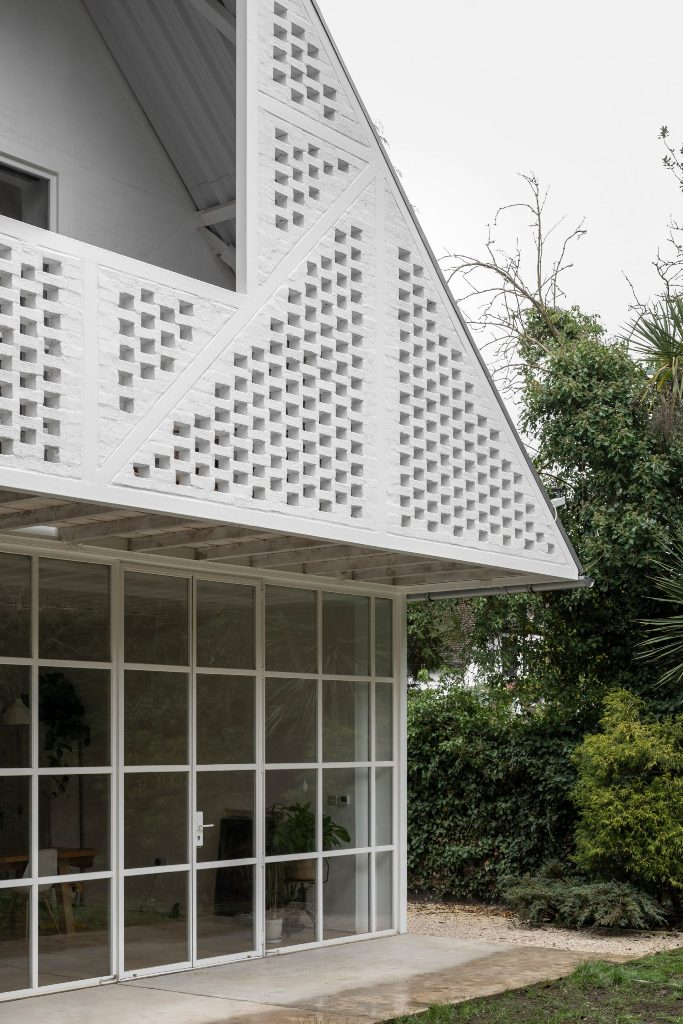 The facade is done with white bricks that imitate Tudor facades of the neighbors