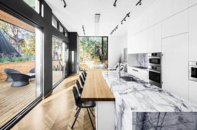 There's a large kitchen-living-dining layout in the extension, it's white and with a white marble kitchen island