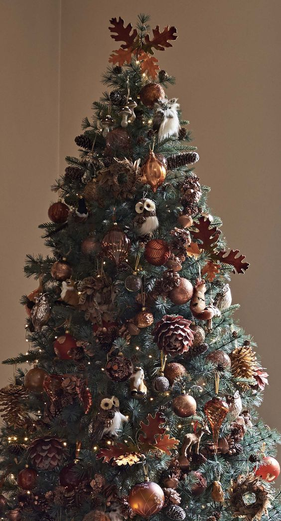 a fabulous fall tree decorated with gold and brown ornaments, plywood leaves, pinecones, lights and faux owls