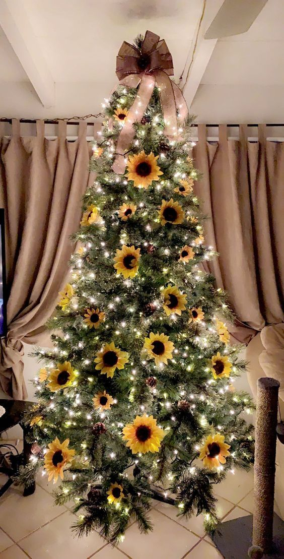 a simple and bright fall tree with lights, pinecones, faux sunflowers and an oversized brown bow on top