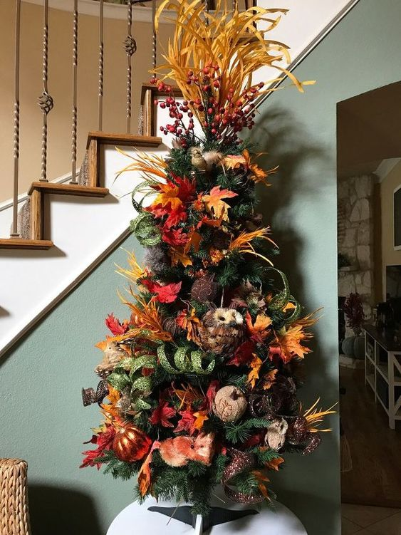 a vintage rustic tree with faux pumpkins, leaves, branches, berries on top and a faux owl is bold