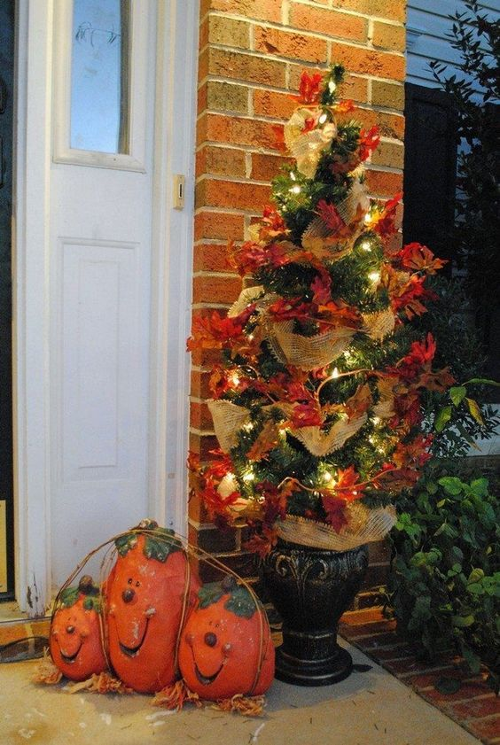 a simple fall or Thanksgiving tree decorated with faux leaves, burlap ribbons and lights is a stylish outdoor decoration