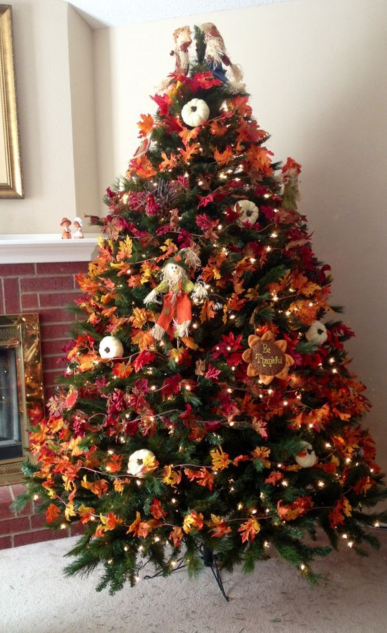 a bold vintage-inspired Thanksgiving tree with lights, bright leaves, pumpkins, faux blooms and a scarecrow