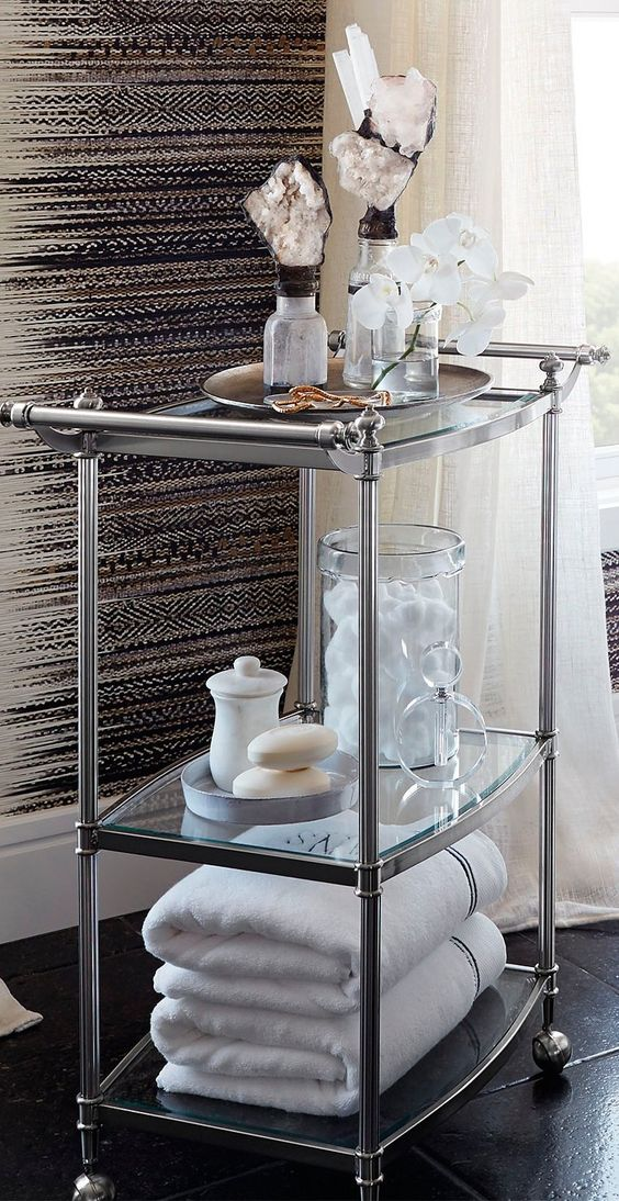 a refined stainless steel and glass rolling cart is a stylish storage piece with many items and some decor