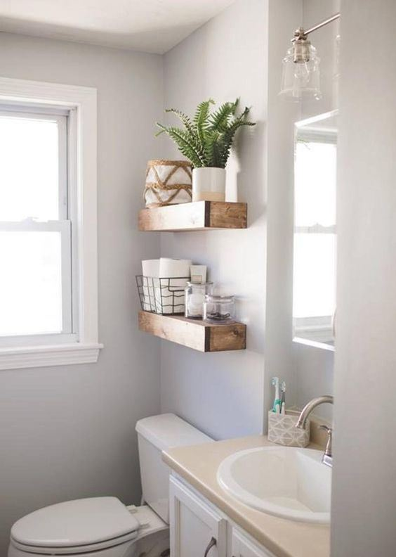 thick wooden open shelves over the toilet give a strong rustic feel to the space