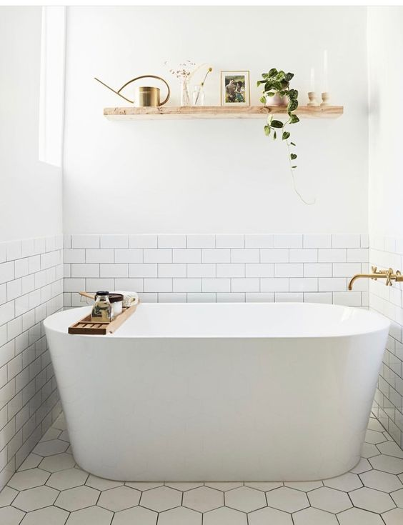 a contemporary neutral bathroom with an open floating shelf over the tub to store and display some decor