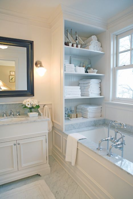 a cabinet with open shelves placed over the tub is a stylish storage unit you may rock