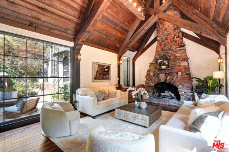 There's a large fireplace, a glazed wall and a mini wooden table