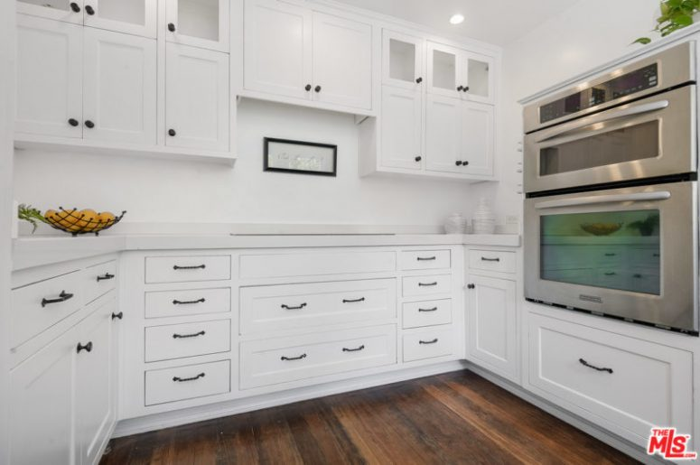 The kitchen is done in white, with chic traditional cabinets and black handles