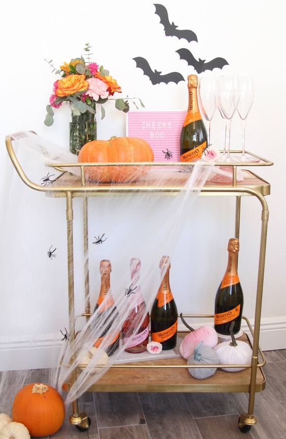a bright Halloween bar cart with a pink sign, velvet pumpkins, bats on the wall, bright blooms and spiderwebs and spiders
