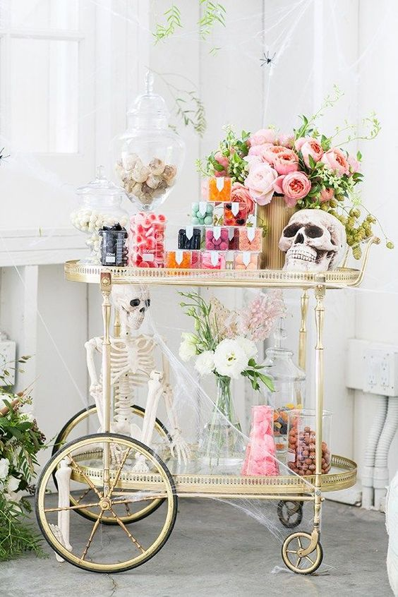 a cute glam Halloween bar with pastel blooms, skulls, a skeleton, lots of candies and sweets with much spiderweb