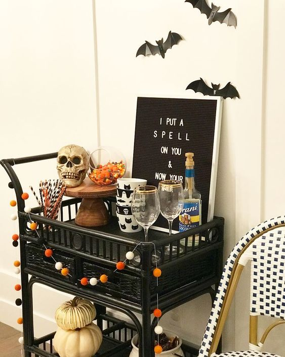 a Halloween bar cart styled with a pompom garland, a skull, a sign, pumpkins and some bats over it