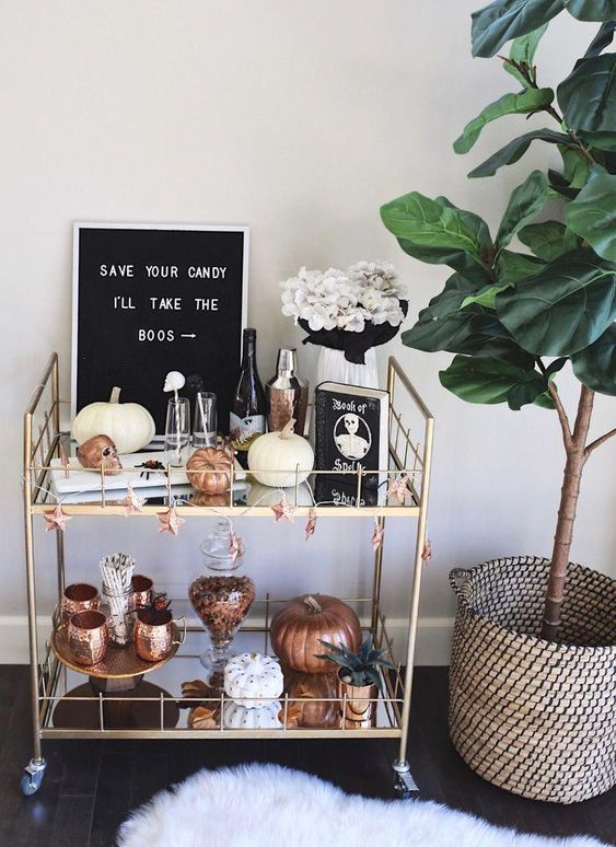 a Halloween bar cart with white and copper pumpkins, a sign, white blooms and skull drink stirrers