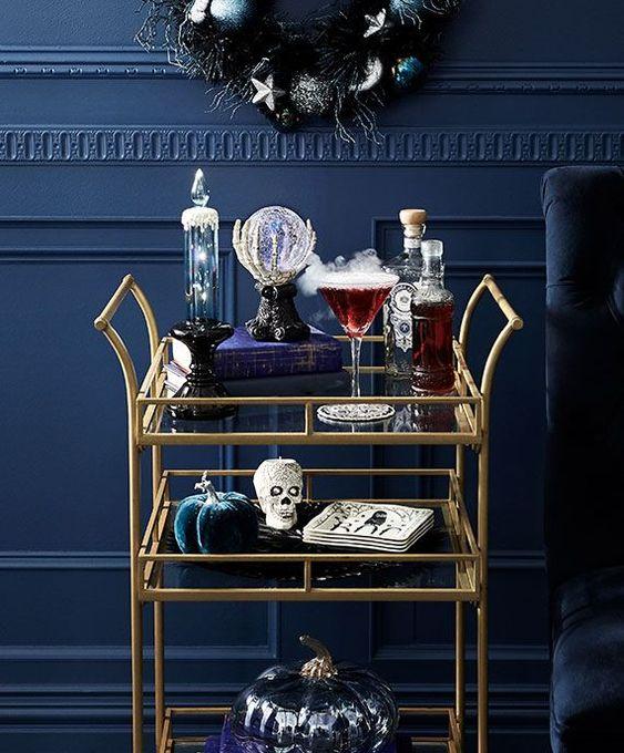 a refined Halloween bar cart with velvet pumpkins, skulls, a crystal ball, smoke and drinks