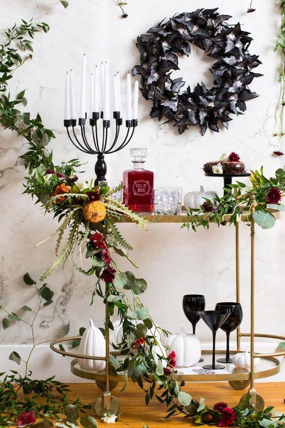 a sophisticated Halloween bar cart with greenery and bright blooms, a candelabra with candles, a black butterfly wreath and sweets and black glasses