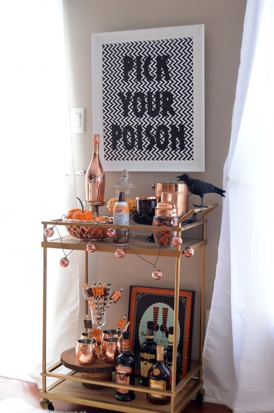 a stylish Halloween bar cart with a pumpkin garland, a crow, copper barware, signs and artworks