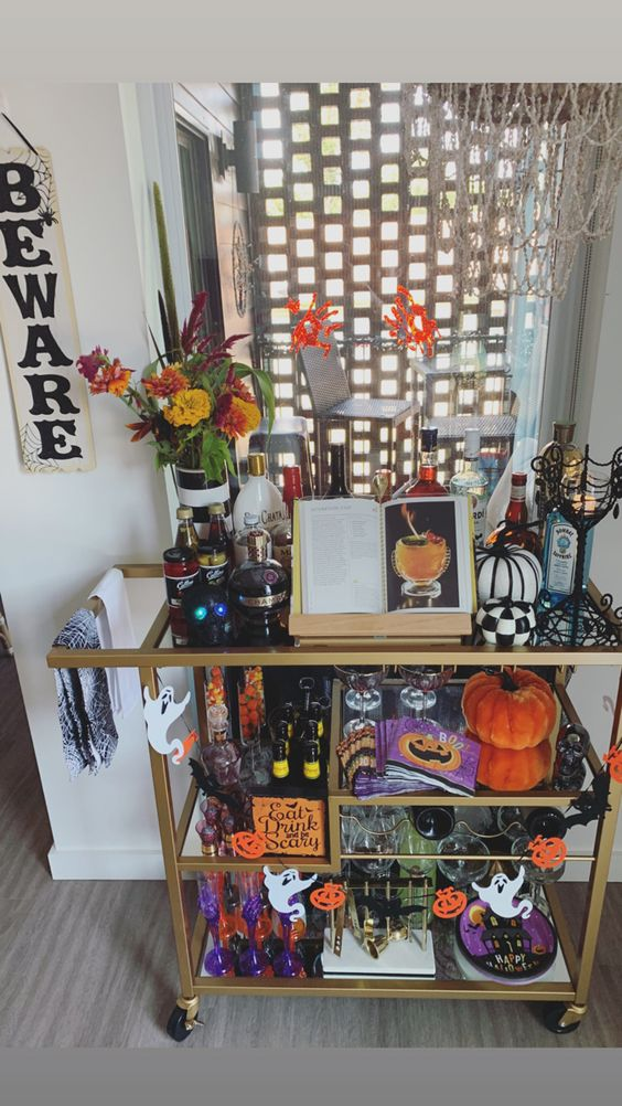 a whimsical bar cart with orange and purple decor, black and white pumpkins, bright napkins and plates and bold blooms