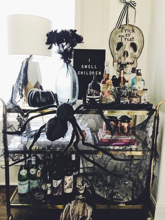 an exquisite Halloween bar cart with a black sign, spiders, black pumpkins, black cheesecloth, dark blooms and lots of drinks