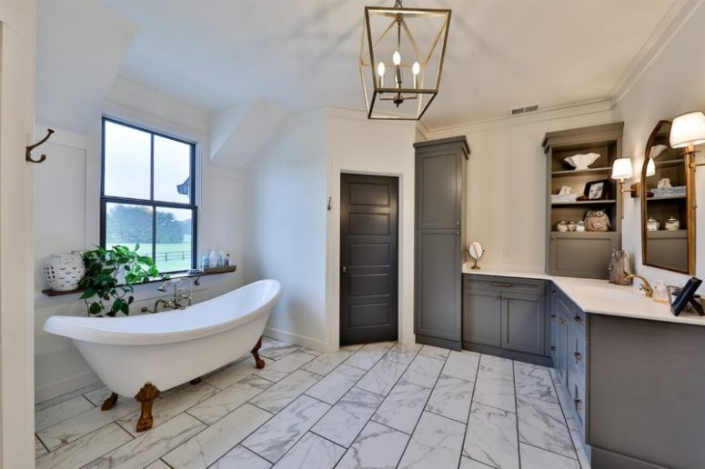 The master bathroom is done with marble tiles, grey furniture, a clawfoot tub and cool views