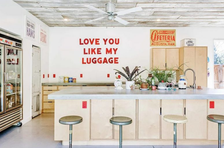 The kitchen is a cozy space with retro touches, plywood furniture and even a shop-like fridge