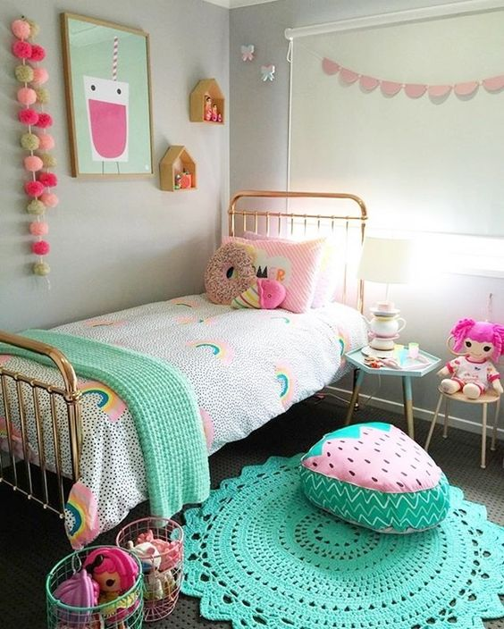 a bright and pastel kid's room with colorful garlands, bedding, toys, rugs and cool foodie pillows