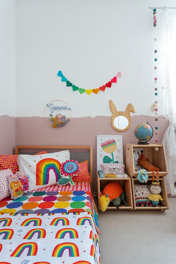 a colorful kid's room with a color block wall, colorful bedding and toys, bright garlands and a bunny mirror