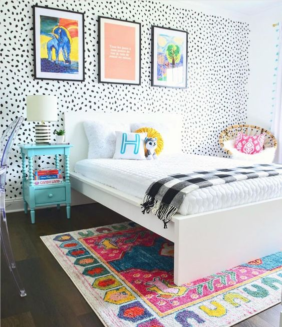 a colorful kid room with a Dolmatin wall, colorful bedding and a rug, bold artworks, a blue nightstand and a rattan chair
