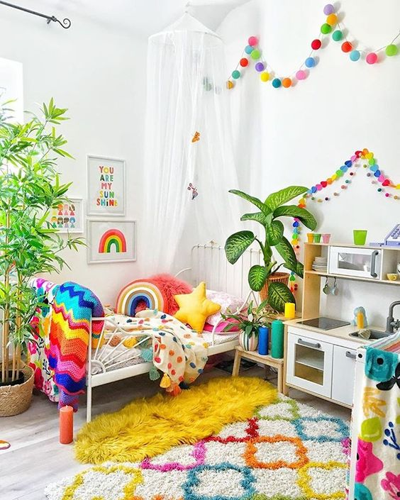 a super bold kid's room with rainbow color garlands, matching bedding, blankets and pillows, a colorful rug and artworks