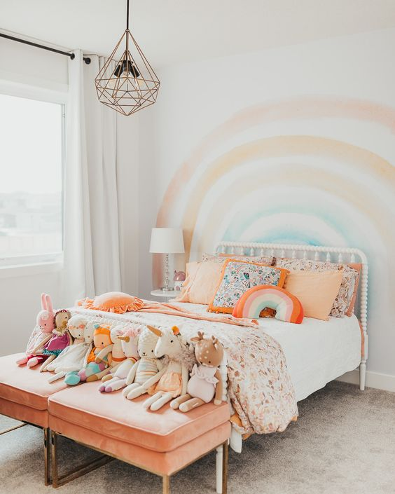 a pastel rainbow kid's room with a rainbow on the wall, colorful bedding and peachy stools with toys