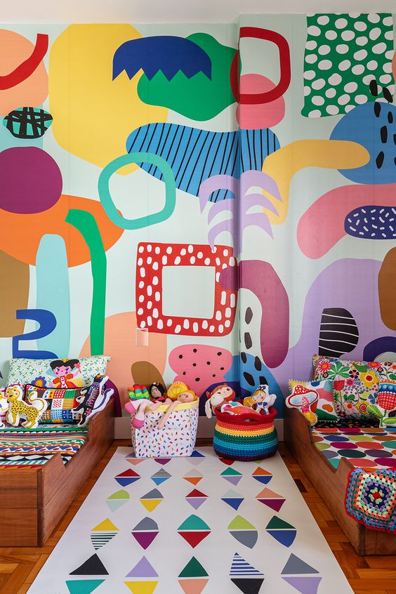 a super colorful shared kid's bedroom with a bold abstract wall, colorful linens and baskets, bold toys