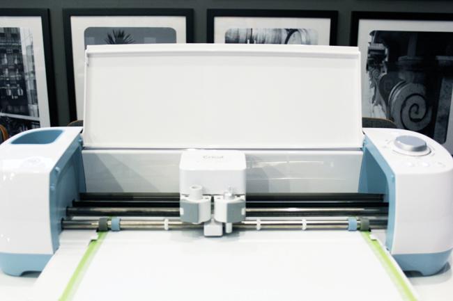 Cricut Explore Air machine cutting white vinyl on green mat