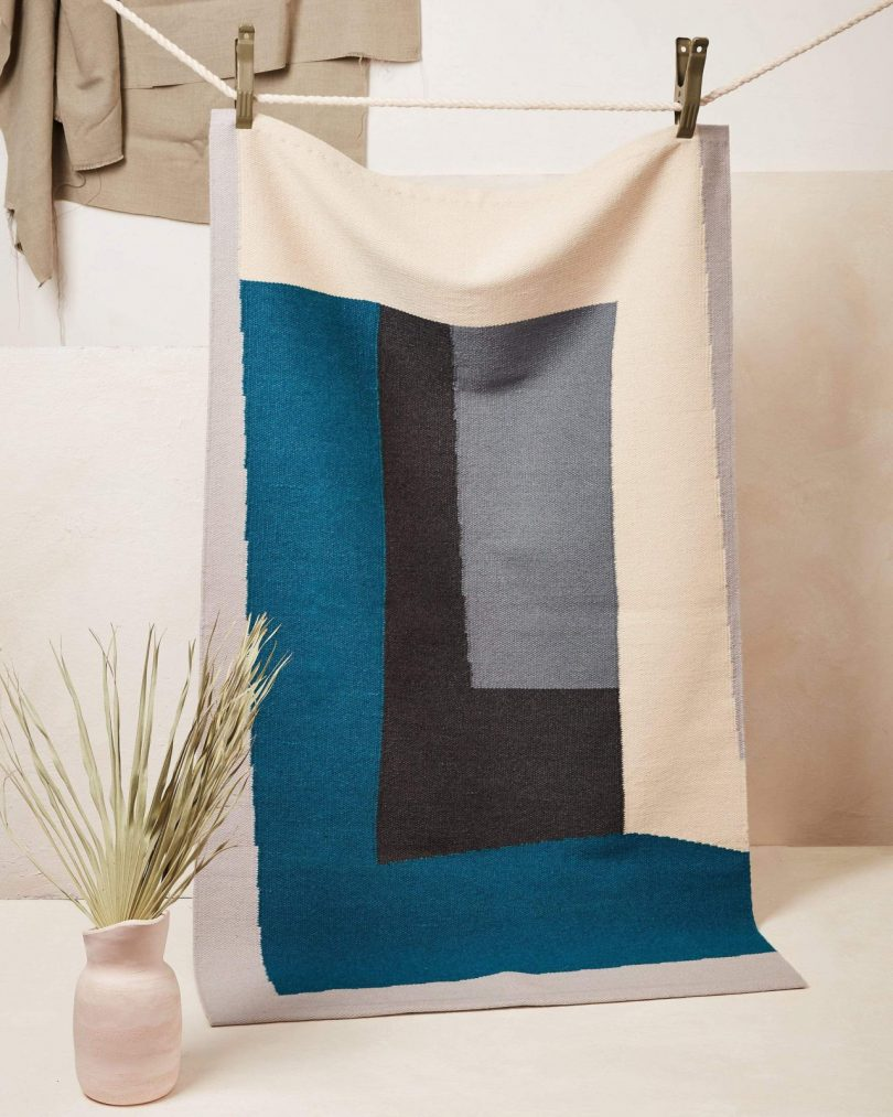 A blue and gray rug hanging on display
