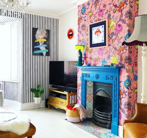 a blue fireplace with colorful tiles and pink floral wallpaper around that accent the hearth even more
