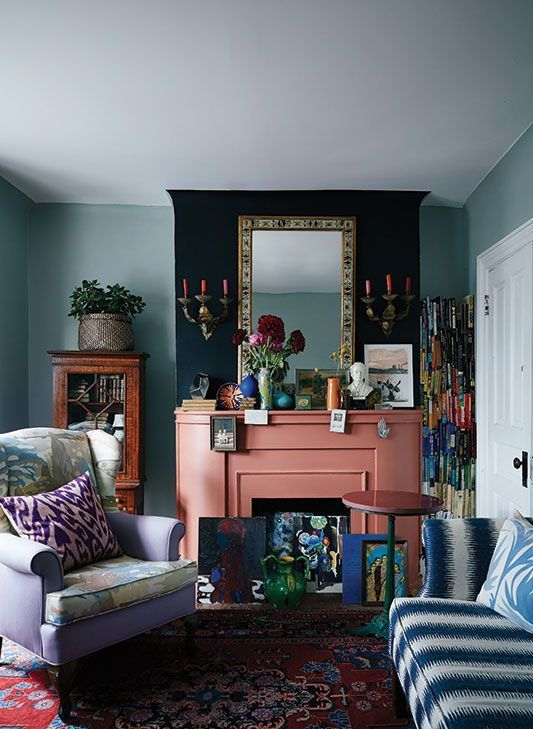 a bright whimsical living room with a slamon pink fireplace and colorful artworks looks unusual and very eye-catchy