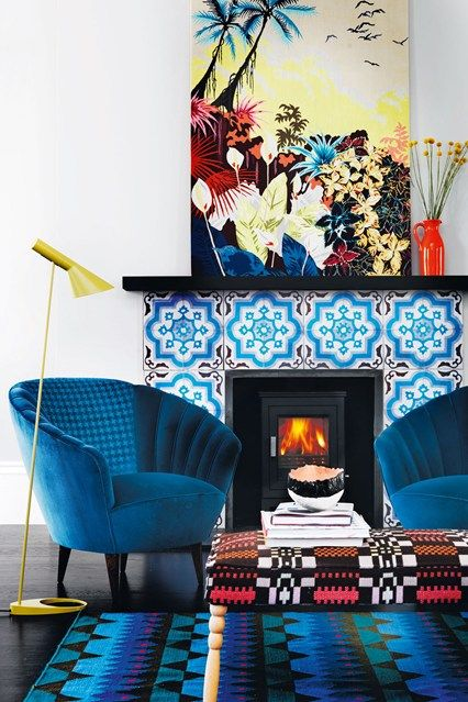 electric blue chairs, a bright blue printed rug, a bold blue tile fireplace and a colorful artwork create color galore that will raise your mood