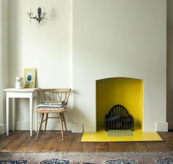 a minimalist fireplace with yellow tiles inside and out brings a warm feeling to the space and adds a bright splash of color