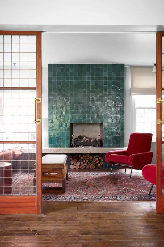 a fireplace clad with green glazed tiles and mid-century modern red chairs that infuse the space with color and make it cozy and welcoming