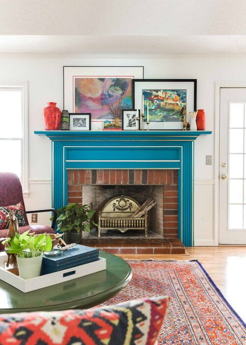 a bright mid-century modern living room with a bold blue mantel with white framing over a brick fireplace for ultimate elegance