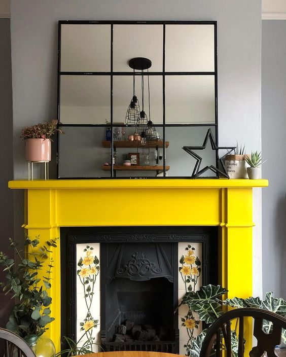 a vintage fireplace with floral tiles on each side and a sunny yellow mantel looks very refined and vintage-inspired