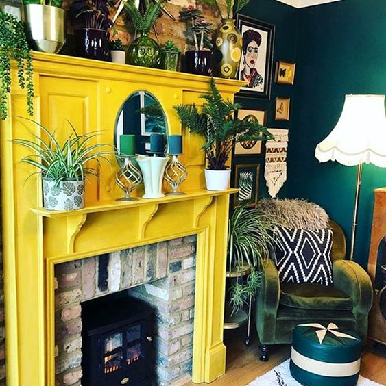 a brick fireplace with a sunny yellow surround, lots of plants and candles is a very cozy idea and a fresh take on a traditional fireplace