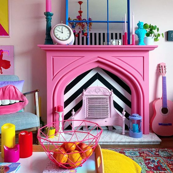 a quirky colorful living room finished off with a hot pink faux fireplace with colorful accessories on the mantel