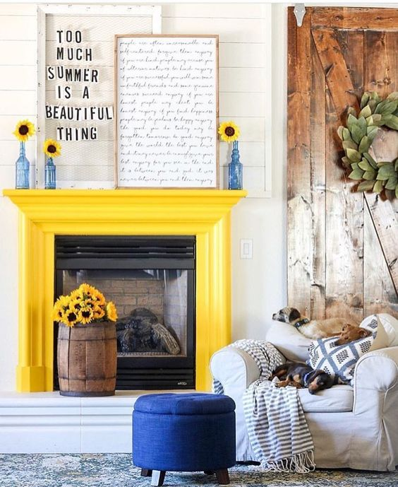 a sunny yellow fireplace, a bold blue ottoman and blue bottles with sunflowers to make the space bolder