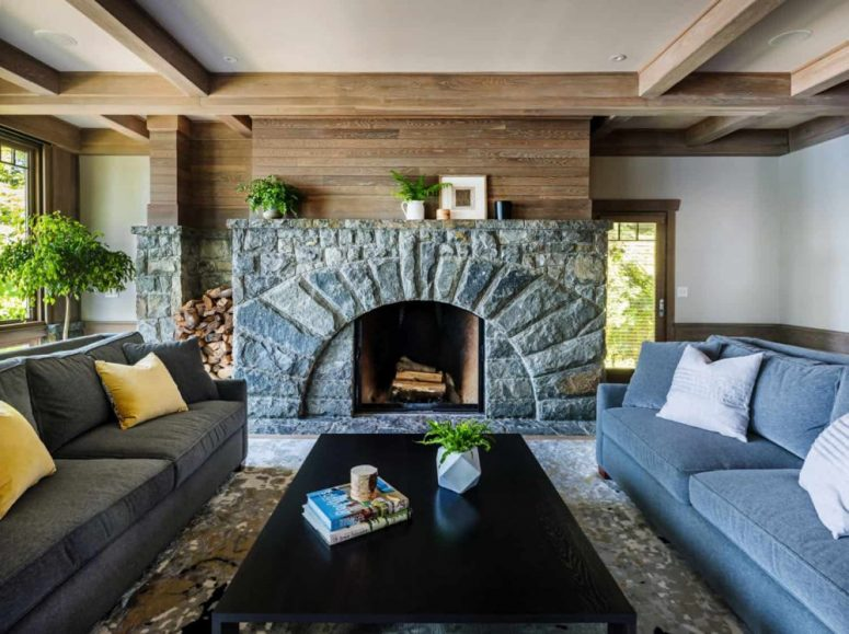 The living room is done with white walls, a wooden wall, a stone clad fireplace, elegant furniture and potted plants