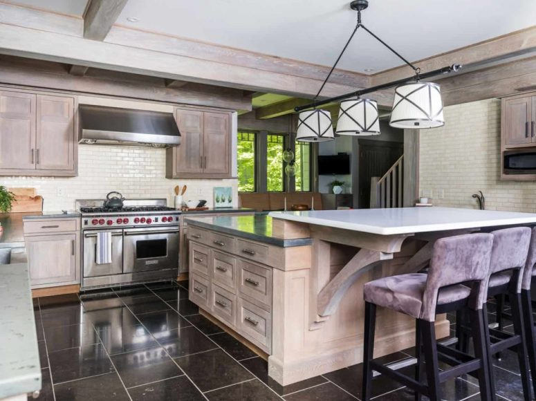 The kitchen is neutral, with farmhouse decor, whitewashed cabinetry and a pendant lamp