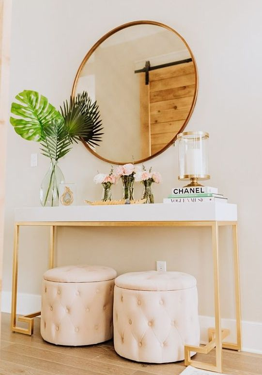 a fabulous modern entryway with a white console, blush storage ottomans, a round mirror and a candle