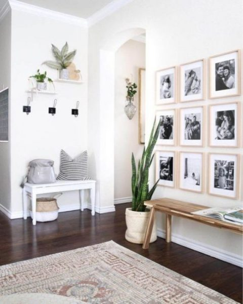 a chic modern entryway with a couple of benches, a gallery wall, some plants and clothes racks