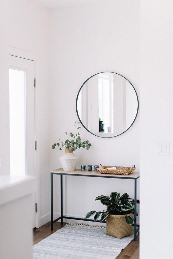a modern front entry with a narrow console, a round mirror, potted plants and baskets is very welcoming
