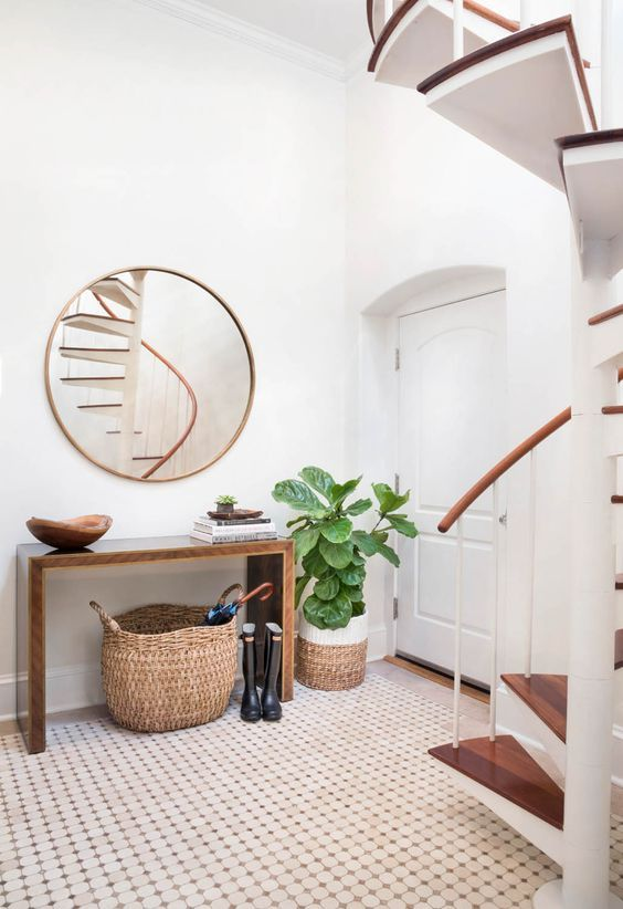 a modern entryway with a wooden sleek console, a round mirror, some baskets and a statement plant